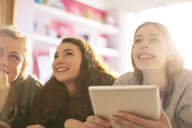 Teenage girls using digital tablet looking up - HOXF00674
