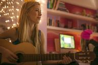 Teenage girl playing guitar in bedroom - HOXF00692