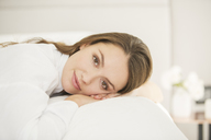 Portrait serene woman laying on bed - HOXF00734