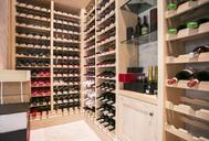 Wine bottles organized on racks in wine cellar - HOXF00758