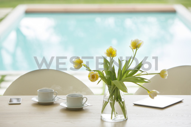 Yellow tulip bouquet and coffee cups on poolside table - HOXF00779 - Tom Merton/Westend61