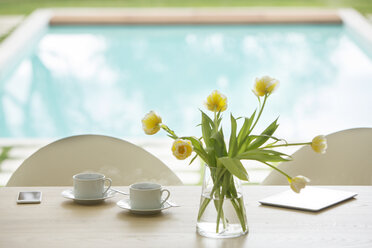 Yellow tulip bouquet and coffee cups on poolside table - HOXF00779