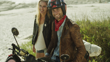 Portrait smiling young couple at motorcycle on beach - HOXF00788