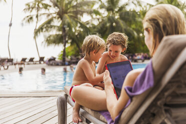 Mother and sons relaxing with digital tablet at poolside - HOXF00791