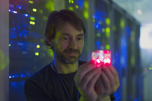 Server room technician holding glowing cube - HOXF00848