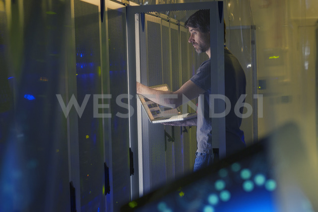 Server room technician with laptop at panel - HOXF00860