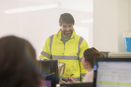 Deliveryman delivering package to businesswoman in office - HOXF00869
