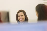 Smiling businesswomen talking in office - HOXF00875