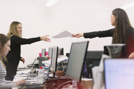 Businesswoman handing paperwork to colleague over computers in office - HOXF00911