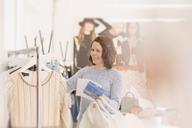 Fashion buyer browsing clothing on rack - HOXF00920