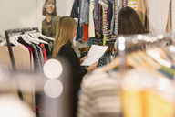 Fashion buyers examining clothing on racks - HOXF00923