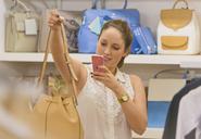 Shopper photographing handbag with camera phone - HOXF00938
