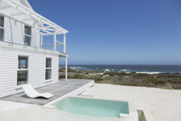 Beach house soaking pool and deck overlooking ocean under sunny blue sky - HOXF00944