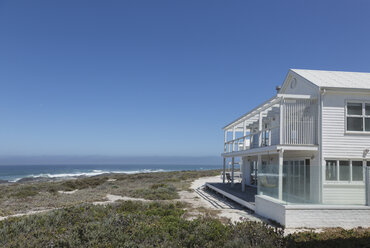 White beach house with ocean view under sunny blue sky - HOXF00950