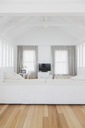 White living room with vaulted wood beam ceiling in home showcase interior - HOXF00956