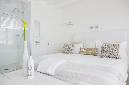 White bedroom with en suite shower in luxury hotel room - HOXF00959