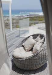 Wicker seat with cushions on sunny beach house deck with ocean view - HOXF00989
