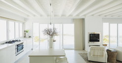 White kitchen with wood beam ceilings in home showcase interior - HOXF00992