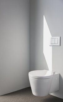 Sunlight on wall above modern toilet in bathroom - HOXF00995