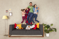 Happy family with two children watching football in living room - BAEF01545