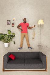 Man at home in his livingroom using smartphone,  listening music - BAEF01551
