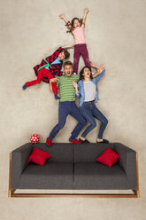 Happy family at home on couch - BAEF01572