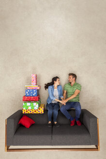 Happy couple sitting on couch with pile of presents - BAEF01575