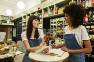 Two smiling women in a store taking notes - EBSF02192