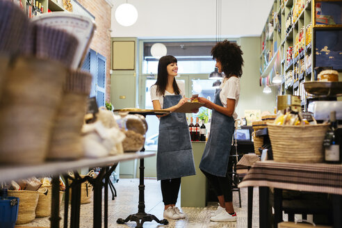 Two smiling women standing in a store with clipboard - EBSF02201