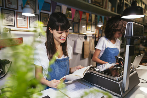 Smiling woman at the counter in a store looking in notebook - EBSF02216