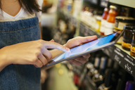 Close-up of woman using tablet at shelf in a store - EBSF02222