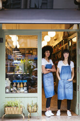 Portrait of two smiling women standing in entrance door of a store - EBSF02228