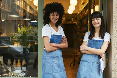 Portrait of two smiling women standing in entrance door of a store - EBSF02231