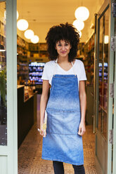 Portrait of smiling woman standing in entrance door of a store - EBSF02234
