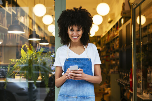 Portrait of smiling woman with cell phone standing in entrance door of a store - EBSF02237