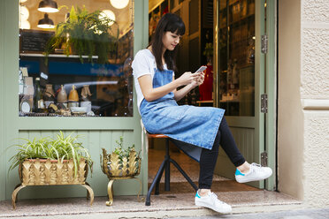 Woman sitting on stool using cell phone at entrance door of a store - EBSF02240