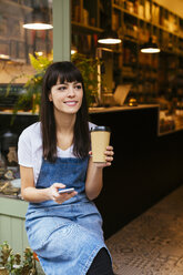 Smiling woman sitting at entrance door of a store holding cell phone and takeaway coffee - EBSF02243
