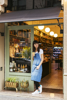 Woman standing at entrance door of a store holding takeaway coffee - EBSF02246