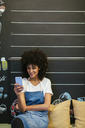 Smiling woman sitting on bench in a store using cell phone - EBSF02252