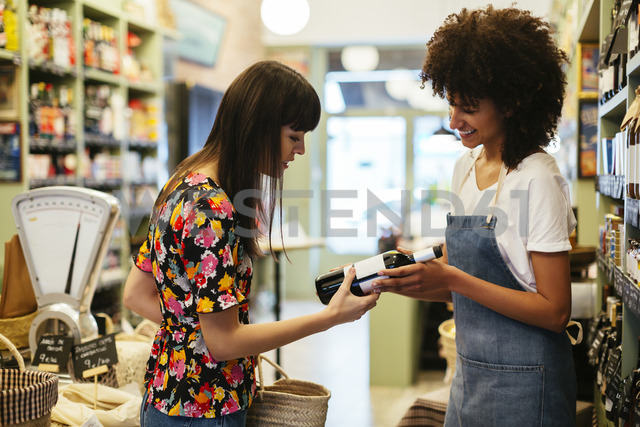 Shop assistant advising customer with wine bottle in a store - EBSF02255