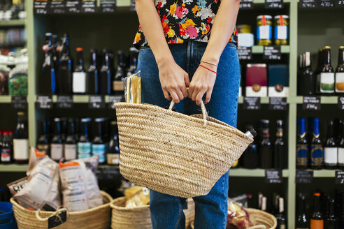 Mid section of customer holding basket in a store - EBSF02264