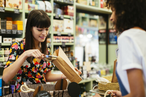Smiling customer filling paper bag at counter of a store - EBSF02267