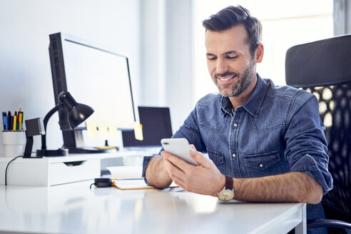 Smiling man using cell phone at desk in office - BSZF00240