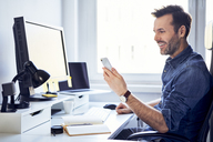 Smiling man using cell phone at desk in office - BSZF00243