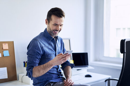 Smiling man using cell phone at desk in office - BSZF00246