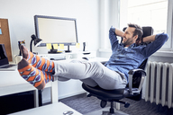 Relaxed man sitting at desk in office looking at computer screen - BSZF00252