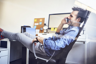 Relaxed man sitting at desk in office talking on cell phone - BSZF00255