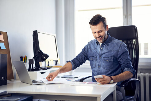 Smiling man with smartphone and draft working at desk in office - BSZF00264