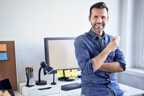Portrait of smiling man with cup of coffee at desk in office - BSZF00270