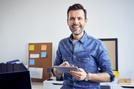 Portrait of smiling man using tablet in office - BSZF00273
